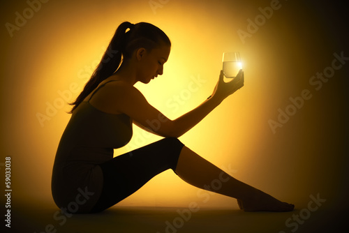 Silhouette of a young woman with a glass of water