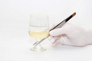 The hand, holds tweezers a glass