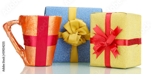 Cup packed in gift paper with gifts isolated on white