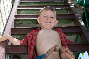 Little boy showing off his dirty feet