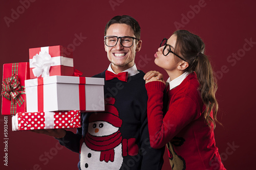 Nerdy woman kissing her boyfriend in christmas time