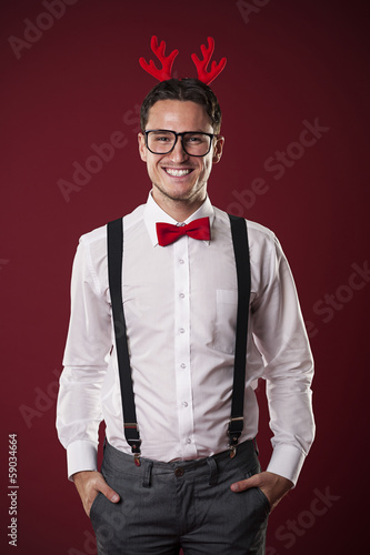 Portrait of smiling nerdy man with christmas horns