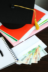 Money for graduation or training on wooden table close-up
