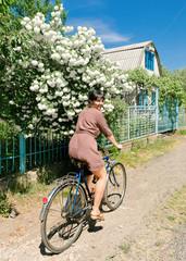 Woman riding a bicycle on a rural lane