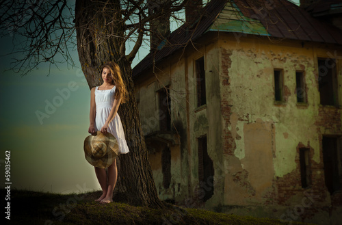 Pretty young woman posing in front of the farm. Attractive girl