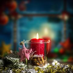 Adventskerze vor weihnachtlich geschmücktem Fenster