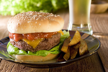 Closeup of a burger with fries and a beer.