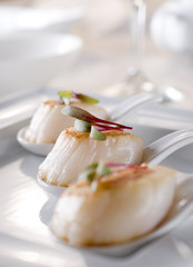 scallop appetizers garnished with sprouts.
