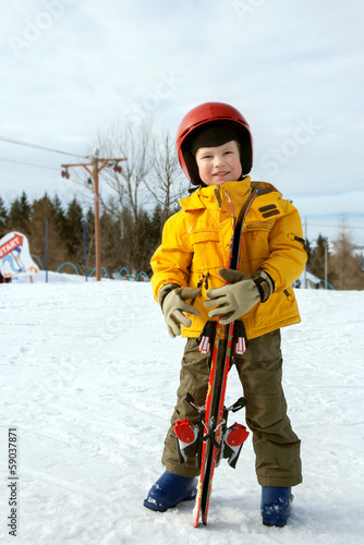 The boy with ski stands on slope