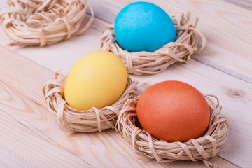 Three Easter eggs in small nests on wooden background