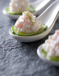 crab salad appetizers on a slice of cucumber on a spoon.