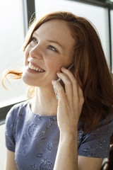 Young Woman with Beautiful Blue Eyes Talking on Cell Phone