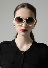 Fashion woman portrait wearing sunglasses on gray