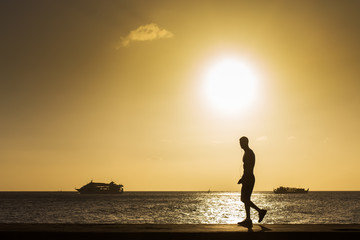Silhouette Man walking on the beach at sunset