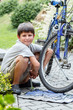 Teenager repairing his bike, changing broken tyre