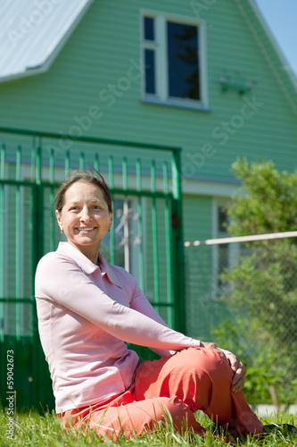 Happy woman sitting in front of new home
