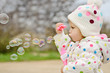 toddler girl blowing soap bubbles