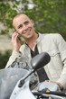 Young man with motorcycle phoning