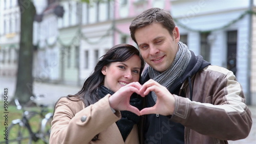 Happy couple holding heart with hands