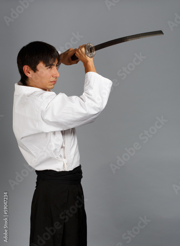 Man in aikido uniform with katana sword