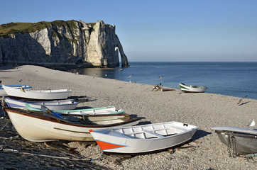 Small boats on pebble beach of Etretat in France
