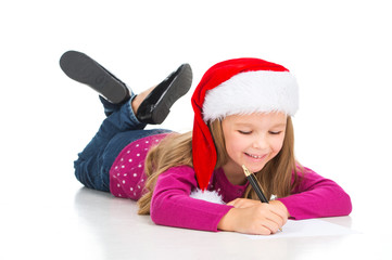 Beautiful little blond girl writing letter to Santa Claus.=