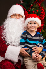 Little funny boy sitting on Santa Claus laps.