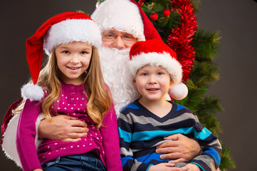 Old kind Santa Claus holding two little kids on his knees.