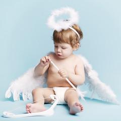 Beautiful little angel on blue background