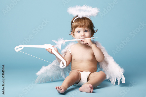 Beautiful little angel on blue background