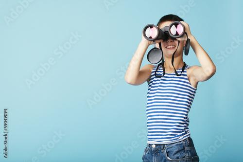 Leinwanddruck Bild little sailor with binoculars on sky blue background