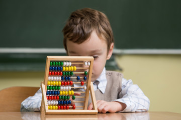 boy in school working with abacus