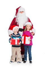 Old Santa Claus hugging little boy and girl with presents