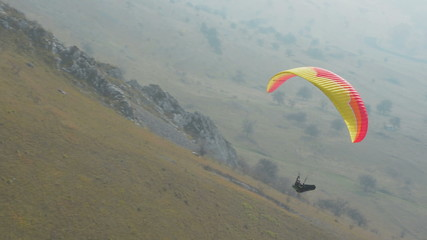 Paraglider running and taking off hill at Remeata, Romania