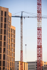Construction site with cranes. In vertical format.