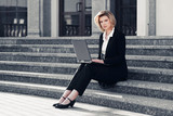 Blond business woman using laptop on the steps