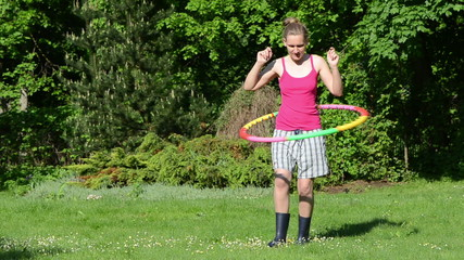 cheerful smiling woman spin hula hoop ring on waist in garden