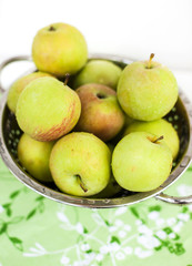 Fresh green apples in a colander