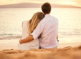 Fototapety Young couple in love on the beach sunset