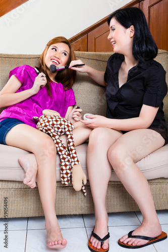 Two asian indonesian girls home using make up