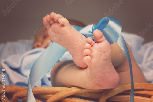 Newborn feet tied with ribbon