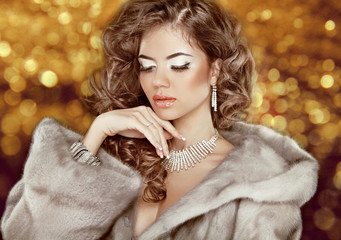 Luxury fashion beauty woman in fur coat over golden bokeh backgr