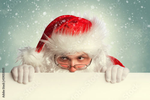 Santa Claus holding white blank banner looking around