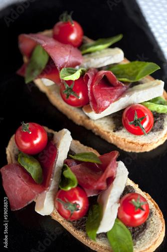 Tartines avec tapenade, tomate, jambon et fromage