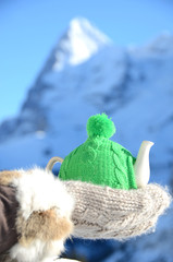 Tea pot in the knotted cap in the hand against alpine scenery