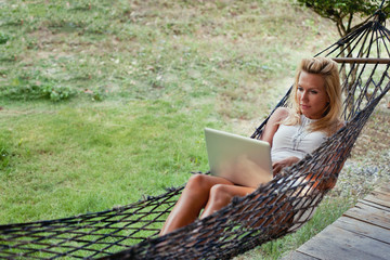 young blond woman with laptop in hammock