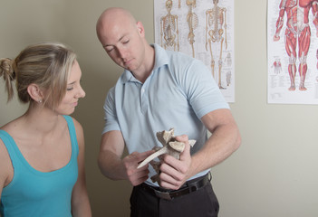 Chiropractor showing female patient  sample spine