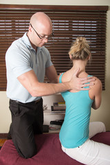 Chiropractor adjusting the female patient spine
