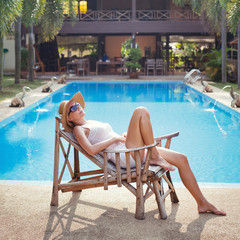 woman in the deck chair near the swimming pool