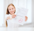 smiling little student girl with test and A grade
